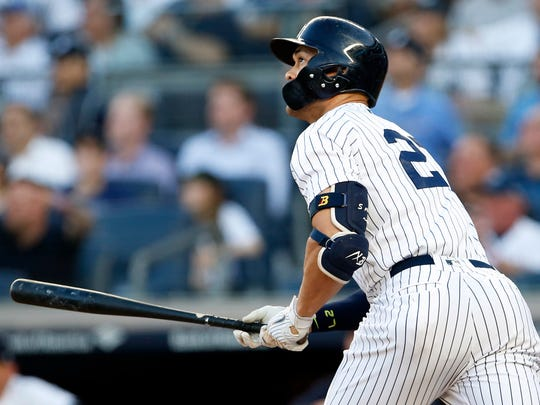 New York Yankees designated hitter Giancarlo Stanton (27) watches a solo home run against the Seattle Mariners during the first inning at Yankee Stadium.