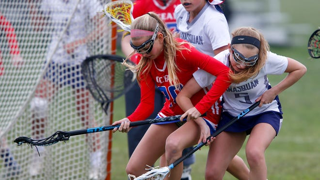 Manasquan's Kennedy Miller (right) tangles with Ocean's Jamie Richter during their game at the National Guard Training Center in Sea Girt Thursday, April 27, 2017.