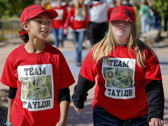 Teagan Frasure, left, and Taylor Bailey stroll together during Under the Big Sky Buddy Walk make their way around the campus of the University of Great Falls. The 2018 Buddy Walk takes place Saturday, Sept. 15