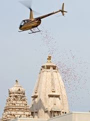 A helicopter drops rose petals and holy water, blessing