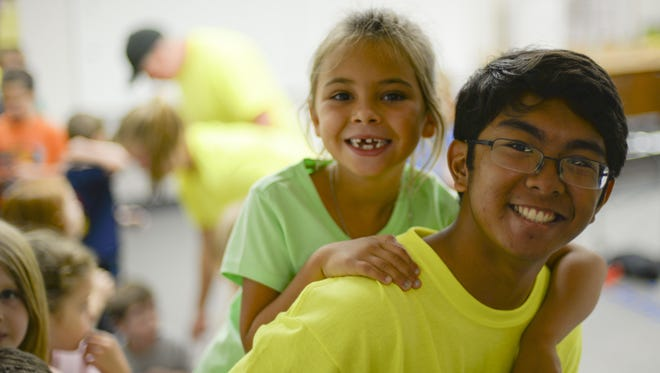 Joseph, a volunteer at the base chapel's vacation bible school, gives Lorelai, a child attending the VBS program, a piggyback ride to her next activity station at Holloman Air Force Base, N.M., on July 20. Many of Holloman Chapel's VBS volunteers regularly attend the chapel's religious services. (Last names are being withheld due to operational requirements).