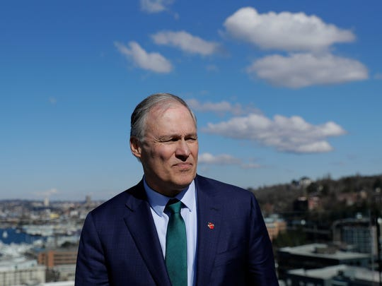 Washington Gov. Jay Inslee stands on an outdoor patio,