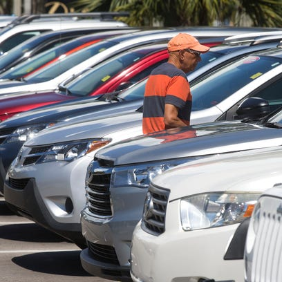 A customer peruses a used car lot while having his