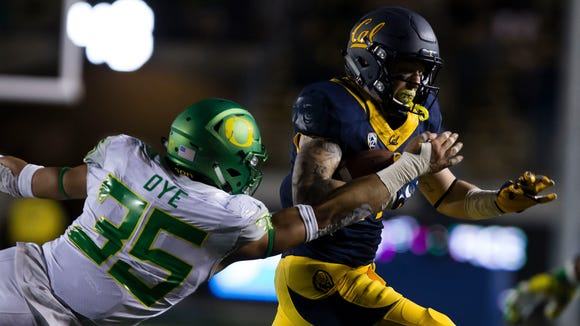 Oct 21, 2016; Berkeley, CA, USA; California Golden Bears wide receiver Vic Wharton III (17) carries the ball against Oregon Ducks linebacker Troy Dye (35) during the fourth quarter at Memorial Stadium. The California Golden Bears defeated the Oregon Ducks 52-49 in overtime. Mandatory Credit: Kelley L Cox-USA TODAY Sports