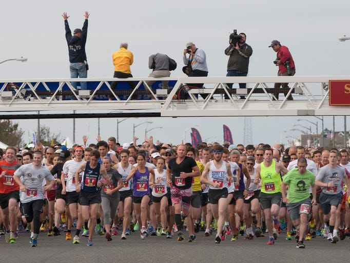Runners head off on the start of the Spring Lake Five in Spring Lake, NJ on May 24, 2014.  Photo by Peter Ackerman