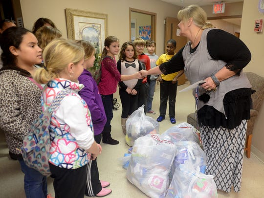 Gail Gustafson of the Dream Center shakes hands with Medina Middle School fourth-graders and thanks them for bringing in new socks Tuesday for Kid President's Socktober initiative.