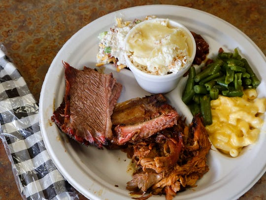 A plate of barbecue brisket, ribs and pulled pork with sides of potato salad, baked beans, green beans, macaroni and cheese and banana pudding Thursday, March 19, 2015, at D and R Market, 105 N. Creasy Lane, Lafayette.