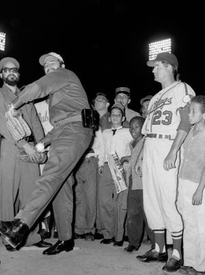 Fidel Castro tossing the ceremonial first pitch before a game against the Rochester Red Wings on April 20, 1960, as Rochester Red Wings manager Clyde King looks on.