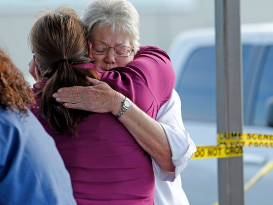 Employees and friends console each other after the attack at Vaughn Foods in Oklahoma.