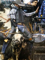 J.W. Harris rides a bull during the Cinch Chute-Out Saturday, Feb. 17, 2018, at Foster Communications Coliseum. Harris was the bull riding champion.