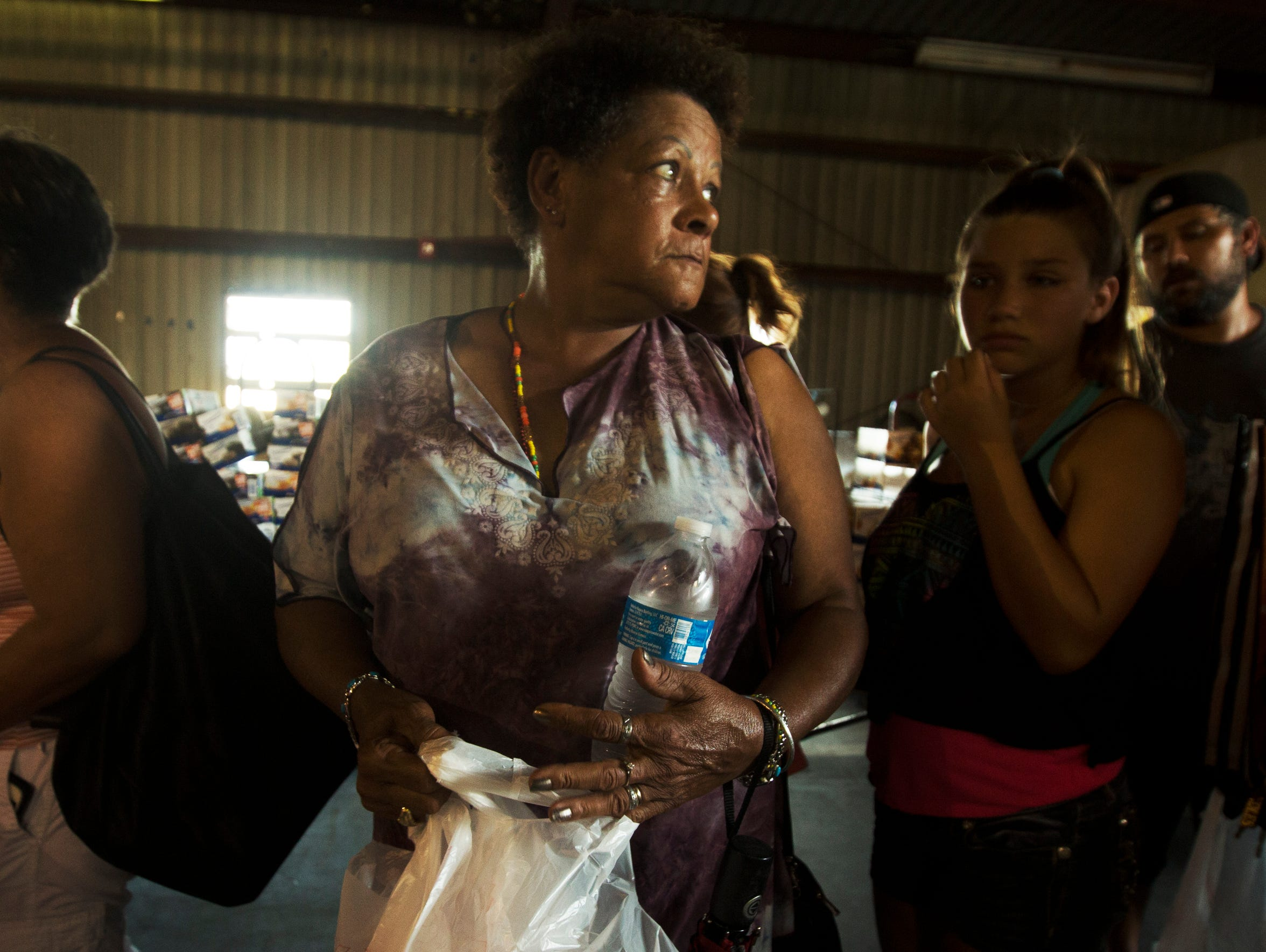 Cape Coral resident, Rose Inoa, center, waits in line
