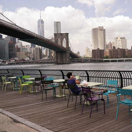 People relax near the water in DUMBO, an acronym for Down Under the Manhattan Bridge Overpass, on August 19, 2014 in the Brooklyn borough of New York City.
