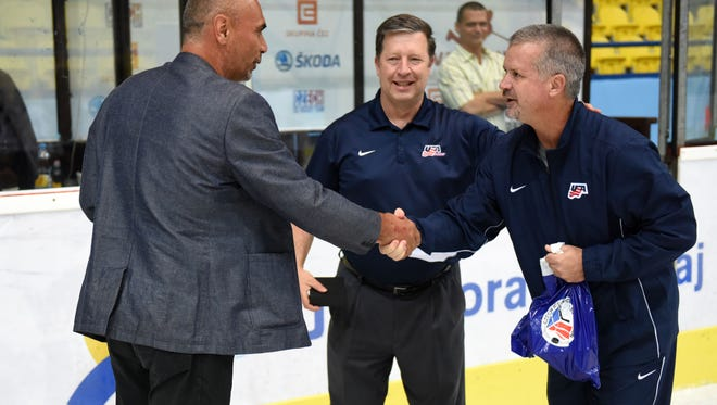 Kevin Krueger (far right) after being honored by USA Hockey's Kevin McLaughlin (center) and a Czech Republic team director, following Krueger's 100th game with the national program.