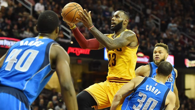 Cleveland Cavaliers forward LeBron James (23) drives to the basket against Dallas Mavericks guard Justin Anderson (1) and guard Seth Curry (30) during the first half at Quicken Loans Arena.