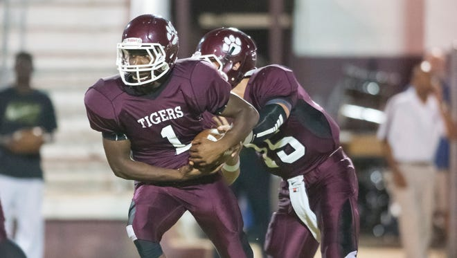 Pensacola High School's Kevon Abrams, (No. 1), left, takes a hand off from Quarterback Slade Harman, (No. 15), right, during a game against Tate High School.