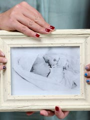 The Thompson family hold a photo of their daughter