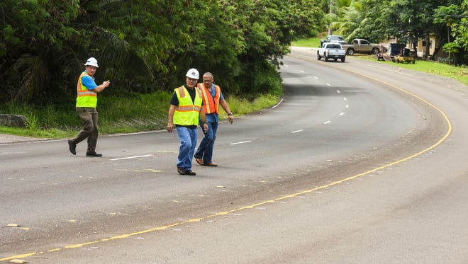 Department of Public Works Director Glenn Leon Guerrero, front, is accompanied by Guam Police Department High Patrol Division Chief Lt. Mike Archangel, right, and WSP USA Lead Engineer Lynden Kobayashi, during a walkthrough of a section of Route 2 in Agat on Friday, June 1, 2018. The trio were at the site to see if any physical changes were needed to reduce the number of serious and fatal crashes that have occurred in the area.
