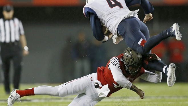 Connecticut Huskies quarterback Bryant Shirreffs (4) is brought down on a run by Cincinnati Bearcats safety Zach Edwards (4) during the fourth quarter of the NCAA football game between the Cincinnati Bearcats and the Connecticut Huskies at Nippert Stadium on the campus of the University of Cincinnati on Saturday, Oct. 24, 2015.
