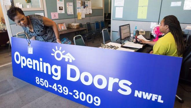 Mya Anderson, of Opening Doors Northwest Florida, gets a good look at the organization's new sign on Friday, May 4, 2018. The EscaRosa Coalition on the Homeless changed its name to better implement and communicate its work.