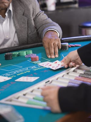 Man gesturing for another card at blackjack table