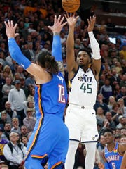 Utah Jazz guard Donovan Mitchell (45) shoots as Oklahoma City Thunder center Steven Adams (12) defends during the second half of an NBA basketball game Wednesday, Oct. 23, 2019, in Salt Lake City. (AP Photo/Rick Bowmer)
