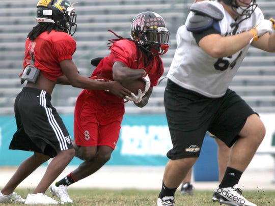South's Ke'Shon Murray, left, hands off to Willie Johnson during practice Tuesday for the John Carrigan Rotary South All-Star Classic in Fort Myers.