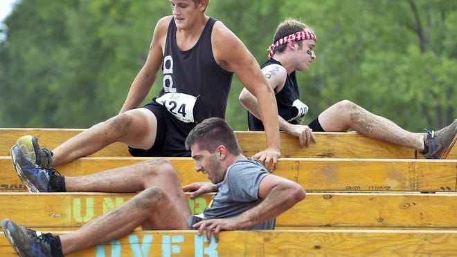 """Barber Beast on the Bay competitors complete the """"Over Under"""" obstacle at Presque Isle State Park near Erie in 2018. This year it's a virtual 5K named Barber Beast on the Block, that participants can run anytime between noon on Friday and noon on Monday."""