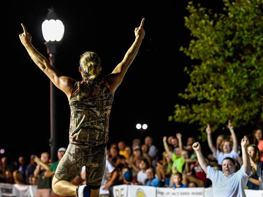 """MIKE LAWRENCE / THE GLEANERPro-elite pole vaulter Sean Young celebrates with the crowd after clearing 17' 3"""" during Friday's Jammin' and Jumping Street vault held at the Henderson riverfront, August 12, 2016."""