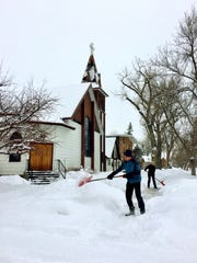 Gary and Jean Dale shovel snow outside Choteau's Lutheran