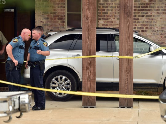 A car is surrounded by crime scene tape while Madison County sheriff's deputies stand outside Little Footprints Learning Center last week after a 2-year-old girl died when her mother left her in the car all day. In separate incidents, two Mississippi children have died as a result of a being left in a hot car in less than two weeks.