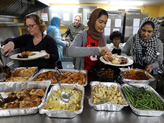 The Bergen County Chapter of the Sisterhood of Salaam Shalom cooked and served food at St. Paul's Community Development Corporation Emergency Men's Shelter in Paterson Monday.  They provided Christmas dinner for approximately two dozen men who reside at the shelter.  The sisterhood is a national Muslim, Jewish, interfaith organization, formed to create peace. Serving the food (from left to right) are, Lori Rosner, of Teaneck, Sarah Huq, 16, of Paterson and her mother, Amber Huq, of Paterson.  Monday, December 25, 2017