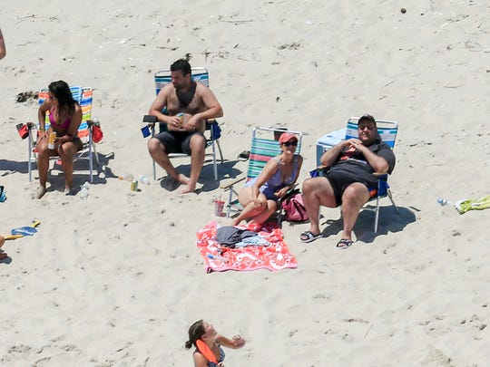 In this July 2, 2017, file photo, New Jersey Gov. Chris Christie, right, uses the beach with his family and friends at the governor's summer house at Island Beach State Park, N.J., when the state park was closed to the public during a government shutdown in New Jersey.