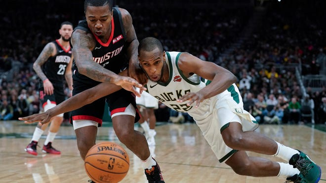 Houston Rockets' Gary Clark and Milwaukee Bucks' Khris Middleton go after a loose ball during the second half of an NBA basketball game Tuesday, March 26, 2019, in Milwaukee. The Bucks won 108-94. (AP Photo/Morry Gash)