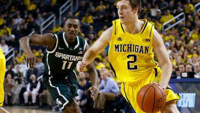 Michigan guard Spike Albrecht (2) moves the ball defended past Michigan State guard Lourawls Nairn Jr. (11) in the first half at Crisler Center.