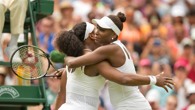 Serena Williams (USA) and Venus Williams (USA) hug at the net after their match on day seven of The Championships Wimbledon at the AELTC.