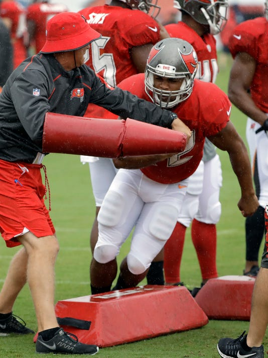 Tampa Bay Buccaneers running back Doug Martin (22) jumps over obstacles as he is hit with pads during an NFL football training camp practice Monday, July 31, 2017, in Tampa, Fla. (AP Photo/Chris O'Meara)