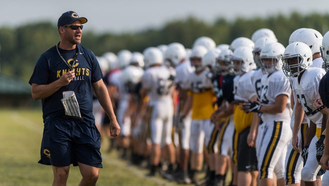 Head Coach Doug Hurt talks to his team before he blows a whistle to start a drill during football practice at Castle High School in Newburgh, Ind., on Monday, Aug. 7, 2017. 