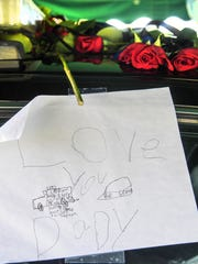 """Love you dady,"" drawn by Jeffrey Hodges, son of Devin Hodges, the Anderson County Sheriff's Office deputy who was fatally injured during a training exercise, left on his squad car before the wake on Monday night at the Civic Center of Anderson."