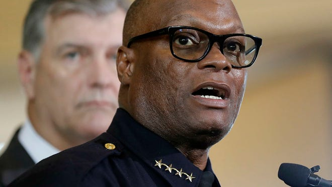Dallas police chief David Brown, front, and Dallas mayor Mike Rawlings, rear, talk with the media during a news conference, Friday, July 8, 2016, in Dallas.