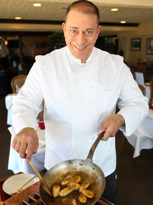 Olive Leaf Bistro chef Jimmy Shraby browns bananas for his banana Foster dessert  in his restaurant along the river front in Jeffersonville, Ind.