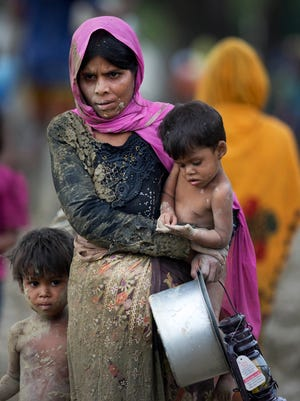 A newly arrived Rohingya family walks towards Balukhali refugee camp in Cox's Bazar, Bangladesh, Wednesday, Sept. 20, 2017. More than 500,000 Rohingya Muslims have fled to neighboring Bangladesh in the past year, most of them in the last three weeks, after security forces and allied mobs retaliated  to a series of attacks by Muslim militants last month by burning down thousands of Rohingya homes in the predominantly Buddhist nation. (AP Photo/Bernat Armangue)