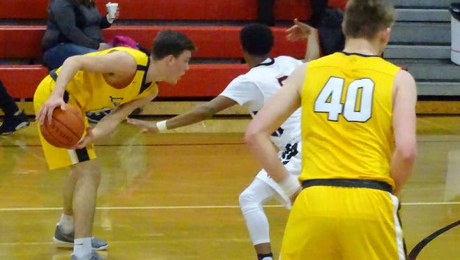 Lancaster's Jacob Arter looks to make a move as Rocky Jorgenson sets a pick during the Golden Gales 66-47 loss to Groveport Tuesday night.