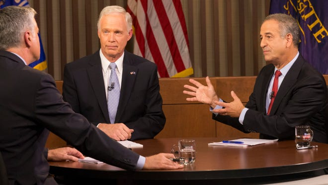 Republican Sen. Ron Johnson (left) and and Democrat Russ Feingold debate earlier this fall at Marquette University with Mike Gousha as moderator.