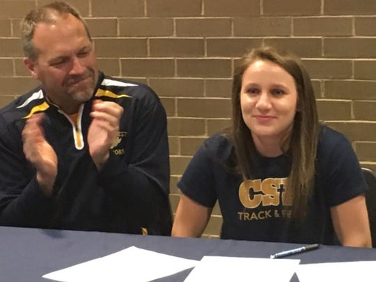 Wausau West's Olivia Bright, right, reacts after signing a national letter of intent with the Concordia University (St. Paul) women's track team Wednesday as Wausau West girls coach John Masanz applauds.