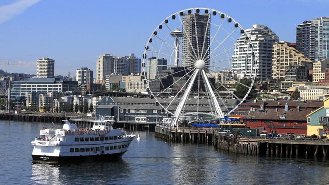 A Ferris wheel is the latest addition to the Seattle waterfront, where the aquarium and a variety of restaurants are just a few steps from the Pike Place Market.