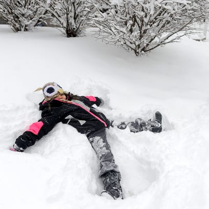 Aurora Graves, 6, makes a snow angel in her front yard