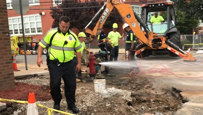 Workers do curb and sidewalk repairs at the intersection of North 10th Street and Brown Avenue July 24.