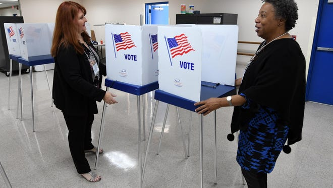 Linda Moreno (left) and Leisha Bean Clark set up voting booths at the Ezell Hester Community Center in Boynton Beach so that early voting can take place in the 2020 Presidential Preference Primary. Saturday, March 7, 2020.