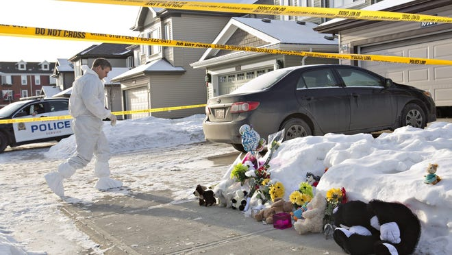 Flowers and stuffed animals lay on the sidewalk as police continue to investigate the scene where multiple shooting deaths occurred in a north Edmonton home, in Edmonton, Alta., on Wednesday, Dec.31, 2014.