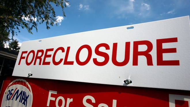 A foreclosure sign on top of a sale sign outside a home in Lakewood, Colorado.